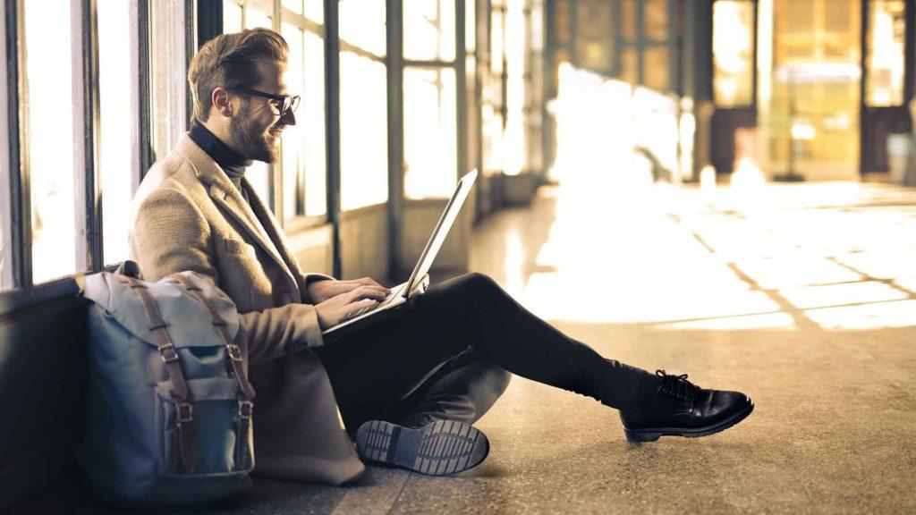 Uomo seduto a terra con laptop, sfondo per sezione Consulenza tributaria
